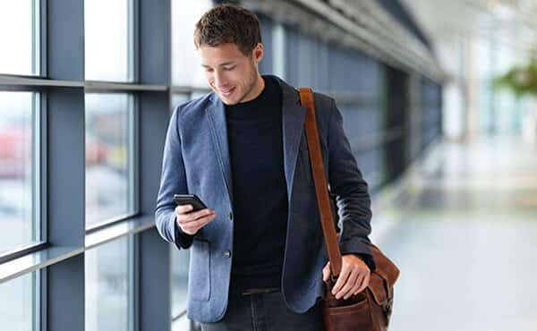 man walking through airport looking at phone